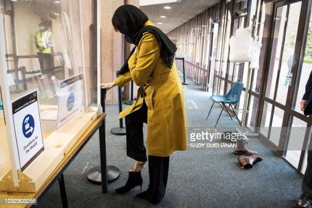 Scotland's First Minister, and leader of the Scottish National Party Nicola Sturgeon, puts on her shoes after visiting Glasgow Central Mosque in...
