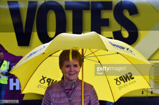Scotland's First Minister and leader of the Scottish National Party , Nicola Sturgeon stands under an umbrella whilst standing in front of the word...