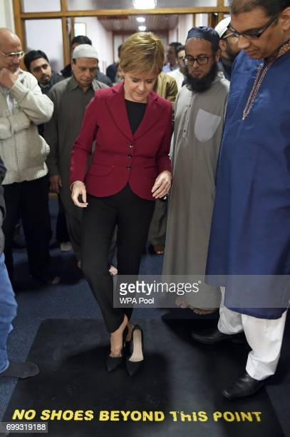 Scotland's First Minister and Scottish National Party leader Nicola Sturgeon puts her shoes on after meeting worshippers during a visit to Dundee...