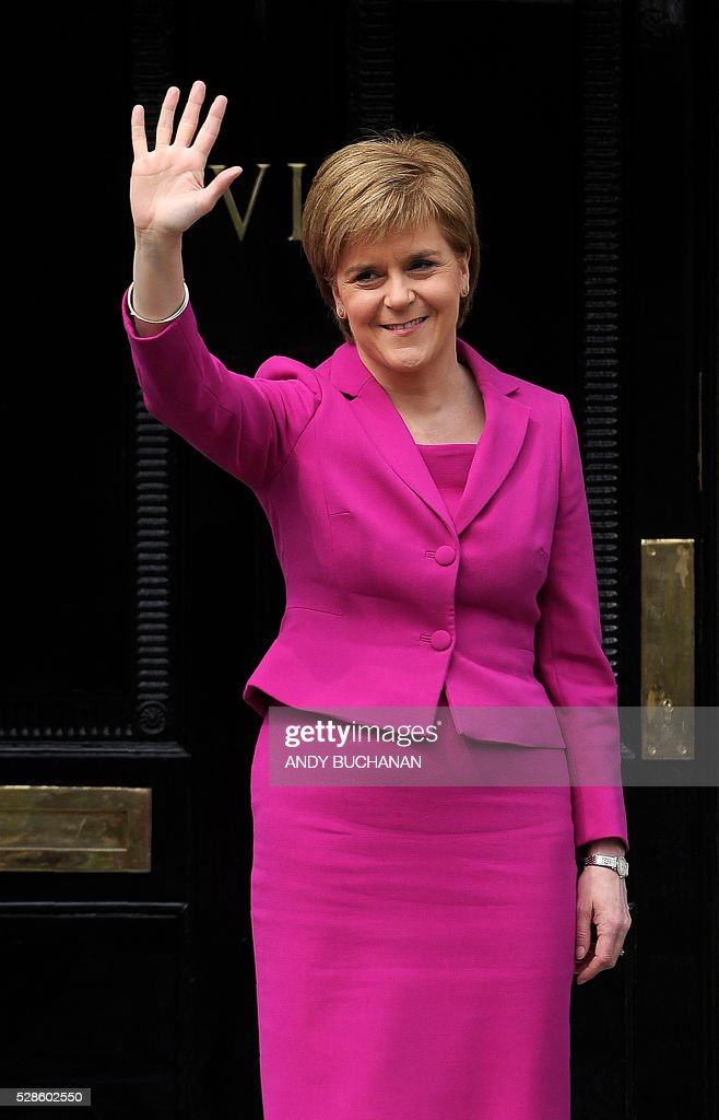 Scotland's First Minister and SNP leader Nicola Sturgeon waves to the media outside Bute House, the official residence of the Scottish First Minister, in Edinburgh, Scotland, on May 6, 2016. Scottish nationalists won a third term in power but lost their outright majority Friday in one of a series of local and regional elections seen as a key test for Labour leader Jeremy Corbyn. / AFP / Andy Buchanan