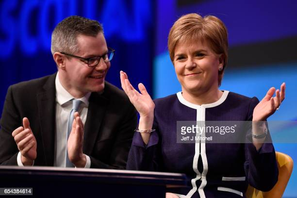 Scotland's First Minister Nicola Sturgeon and cabinet secreatry for finance Derek Mackay listen to Angus Robertson deputy SNP leader addressing...