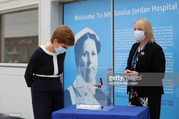 Scotland's First Minister Nicola Sturgeon and field hospital CEO Jill Young, both wearing face masks, view World War I medals given to nurses, during...