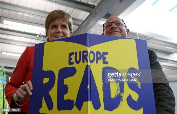 Scotland's First Minister Nicola Sturgeon and Marc Lambert from the Scottish Book Trust hold a mock book with the cover title of Europe Reads as she...