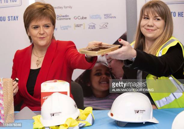 Scotland's First Minister Nicola Sturgeon and Training officer with Moretti Care Zofia Piotrowska pass around a box of Polish chocolates during a...
