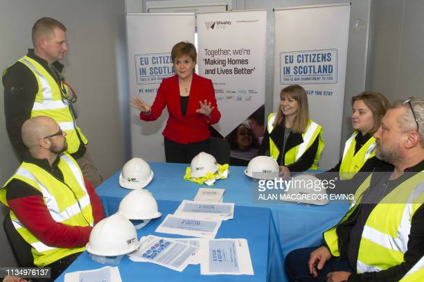 Scotland's First Minister Nicola Sturgeon chats to Polish and Romanian employees during a visit to a building site to make a commitment to EU...