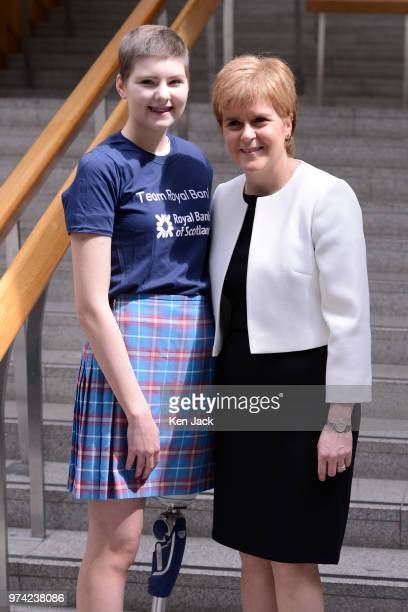 Scotland's First Minister Nicola Sturgeon in the lobby of the Scottish Parliament with 17yearold amputee Johanna Lambe from Edinburgh who has a rare...
