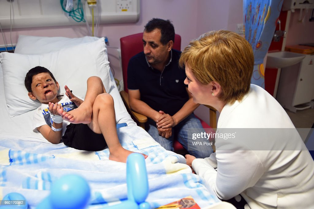 Scotland's First Minister Nicola Sturgeon (R) meets with 4-year-old Mohammad Sudais and his uncle Mohammed Asif during a visit to the Royal Hospital for Children to mark the 70th Anniversary of the NHS on July 5, 2018, in Glasgow, United Kingdom. Mohammad Sudais arrived in Glasgow in 2014 after being seriously injured in a gas explosion in Peshawar. Welsh Labour MP and Health Minister, Aneurin 'Nye' Bevan, formed the National Health Service on 5 July 1948. It is the publicly funded national healthcare system for the UK.