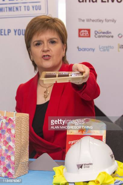 Scotland's First Minister Nicola Sturgeon passes around a box of Polish chocolates during a visit to a building site to make a commitment to EU...