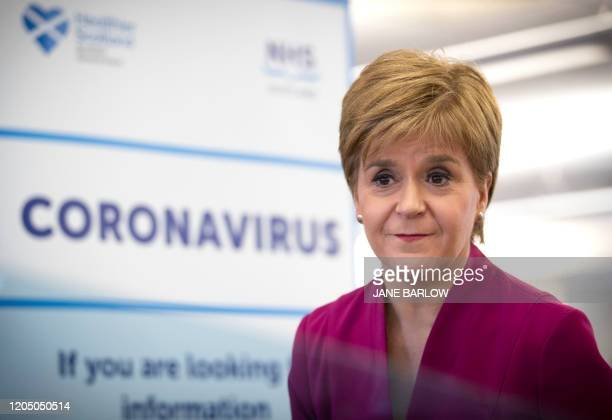 Scotland's First Minister Nicola Sturgeon stands near a sign reading CORONAVIRUS as she speaks during a visit to the NHS 24 contact centre at the...