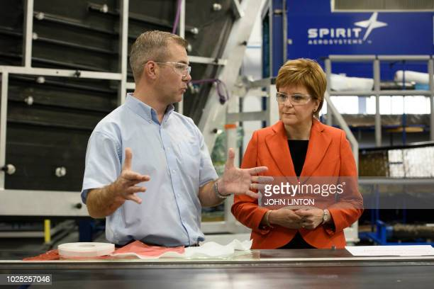 Scotland's First Minister Nicola Sturgeon talks with Stephen Brown an engineer as she visits Spirit AeroSystems near Prestwick Airport on August 30...