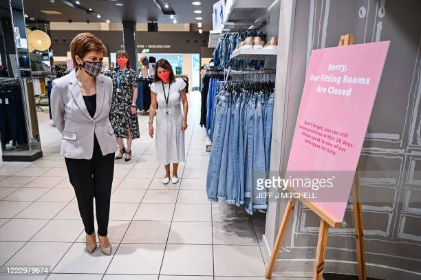 Scotland's First Minister Nicola Sturgeon wearing a Tartan face mask reads a sign explaining fitting room closure as she visits New Look at Ford...