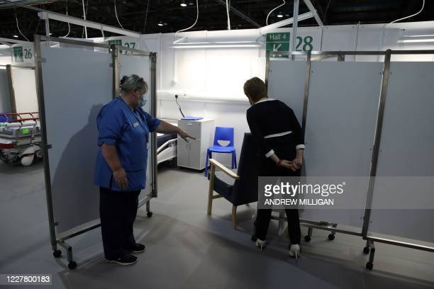 Scotland's First Minister Nicola Sturgeon wears a face mask as she views a cubicle during her visit to the field hospital the NHS Louisa Jordan, set...
