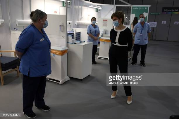 Scotland's First Minister Nicola Sturgeon wears a face mask as she talks to nurses during her visit to the field hospital the NHS Louisa Jordan, set...
