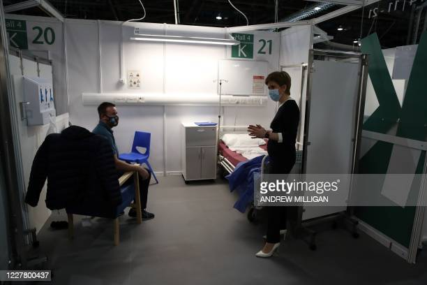 Scotland's First Minister Nicola Sturgeon wears a face mask as she speaks to patient Thomas McShane during her visit to the field hospital the NHS...