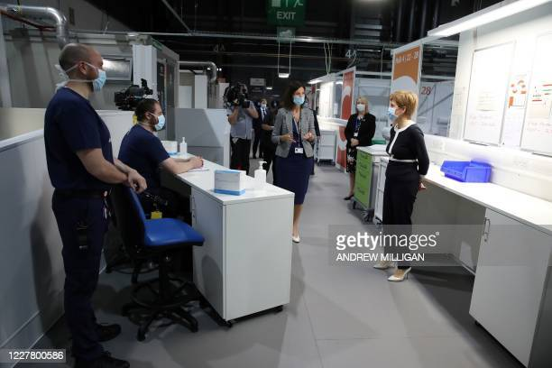 Scotland's First Minister Nicola Sturgeon wears a face mask as she talks to staff during her visit to the field hospital the NHS Louisa Jordan, set...