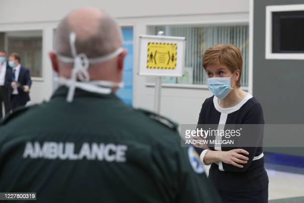 Scotland's First Minister Nicola Sturgeon wears a face mask during as she speaks to paramedics during her visit to the field hospital the NHS Louisa...