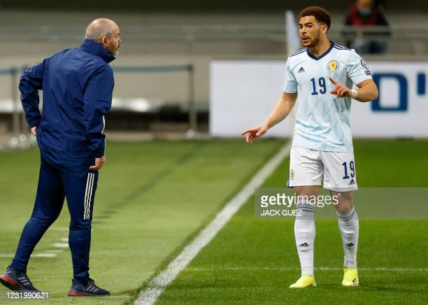 Scotland's forward Che Adams speaks with his coach Steve Clarke during the 2022 FIFA World Cup qualifier group F football match between Israel and...