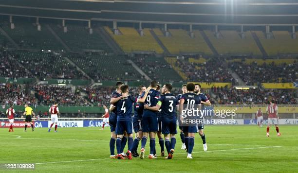 Scotland's forward Lyndon Dykes celebrates scoring the opening goal from the penalty spot with his teammates during the FIFA World Cup Qatar 2022...