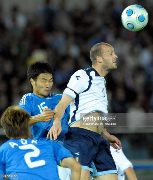 Scotland's forward Steven Fletcher heads the ball beside Japan's defender Yasuyuki Konno and defender Yuki Abe during their Kirin Challenge Cup...