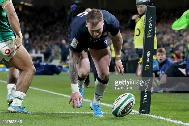 Scotland's fullback Stuart Hogg fumbles the ball and drops it before claiming a try which is subsequently denied after a review during the Six...