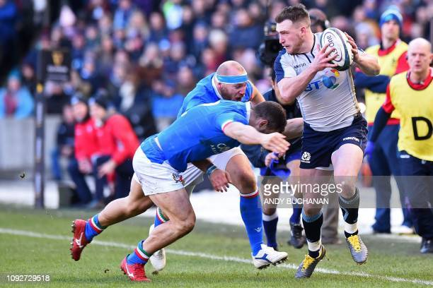 Scotland's fullback Stuart Hogg is tackled during the Six Nations international rugby union match between Scotland and Italy at Murrayfield in...
