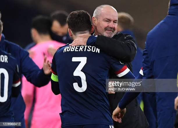 Scotland's head coach Steve Clarke embraces Scotland's defender Andrew Robertson on the pitch after Scotland win the penalty shoot-out during the...