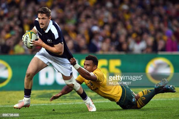 Scotland's Henry Pyrgos is tackled by Australia's Will Genia during their rugby union Test match in Sydney on June 17 2017 / AFP PHOTO / William WEST...