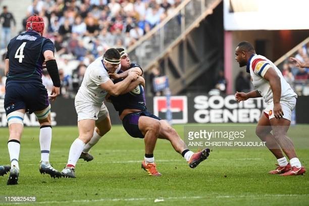 Scotland's hooker Stuart McInally is tackled by France's hooker Guilhem Guirado during the Six Nations rugby union tournament match between France...