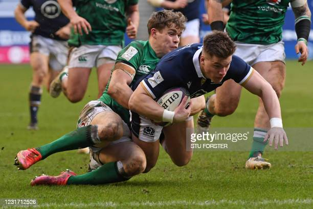 Scotland's Huw Jones dives over the line to score a try despite the tackle from Ireland's centre Garry Ringrose during the Six Nations international...
