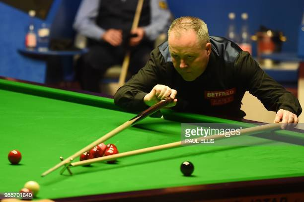 Scotland's John Higgins plays a shot against Wales's Mark Williams plays during the World Championship Snooker final match at The Crucible in...