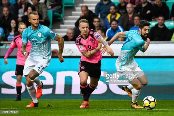 Scotland's Leigh Griffiths vies with Slovenia's Aljaz Struna and Miha Mevlja during the FIFA World Cup 2018 qualifier football match between Slovenia...