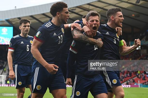 Scotland's midfielder Callum McGregor celebrates with teammates after scoring the equaliser during the UEFA EURO 2020 Group D football match between...