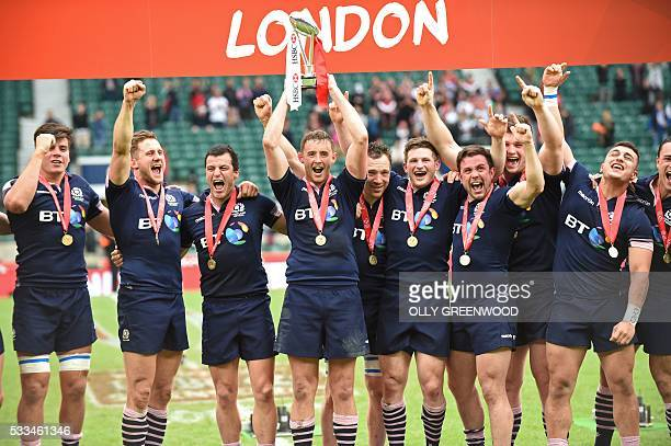 Scotland's players celebrate with the trophy after winning the final of the World Rugby Sevens Series London rugby union tournament between Scotland...
