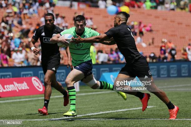 Scotland's Robbie Fergussson runs in for a try in the tackle of New Zealand's Regan Ware during the men's rugby sevens match between New Zealand and...
