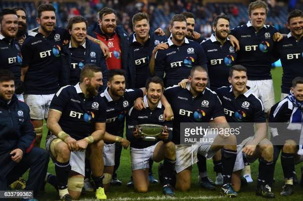 Scotland's scrumhalf Greig Laidlaw holds the cup and poses with teammates after winning the Six Nations international rugby union match between...