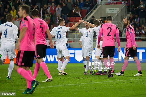 Scotland's Steven Fletcher and Callum Paterson walk past Slovakia's players celebrating their third goal during the WC 2018 football qualification...
