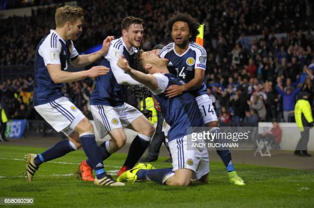 TOPSHOT Scotland's striker Chris Martin celebrates with teammates after scoring the only goal of the World Cup 2018 qualification football match...