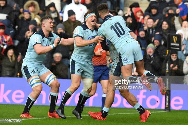 Scotland's Stuart McInally celebrates with teammates after scoring a try during the Six Nations international rugby union match between Scotland and...