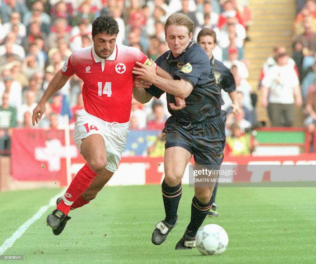 Scotland's Thomas Boyd (R) and Switzerland's Kubilay Turkyilmaz struggle for the ball during their European soccer championship match, the last one in group A, in Birmingham, England, 18 June.