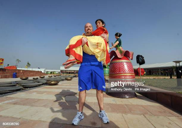 Scotland's weightlifter Tommy Yule poses with a local girl in traditional costume at the Athlete's Village in New Delhi, India.