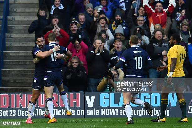 Scotland's wing Byron McGuigan celebrates with Scotland's fullback Sean Maitland after scoring their first try during the autumn international rugby...