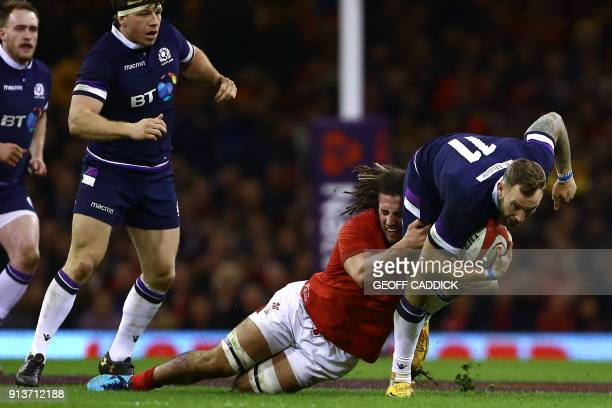 Scotland's wing Byron McGuigan is tackled by Wales' flanker Josh Navidi during the Six Nations international rugby union match between Wales and...