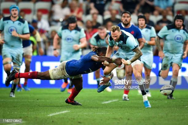 TOPSHOT Scotland's winger Byron McGuigan is tackled by France's winger Alivereti Raka during the 2019 Rugby World Cup warmup test match between...