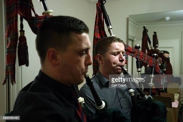 Scots Guardsmen practice on their bagpipes as they prepare to perform in a practice session at Cadogan Hall on December 2 2015 in London England...