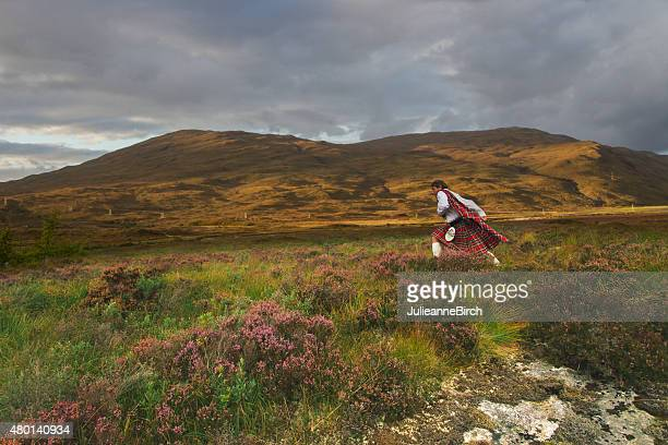 scotsman running across the moors - kilt stock photos and pictures