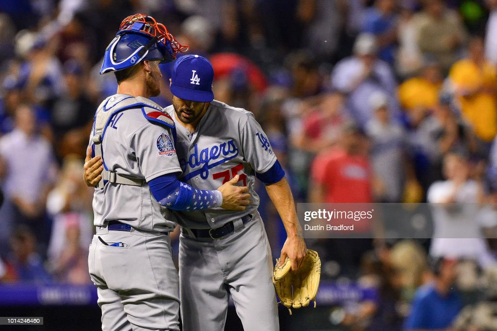 Scott Alexander #75 and Yasmani Grandal #9 of the Los Angeles Dodgers celebrate after an 8-5 win over the Colorado Rockies at Coors Field on August 9, 2018 in Denver, Colorado.
