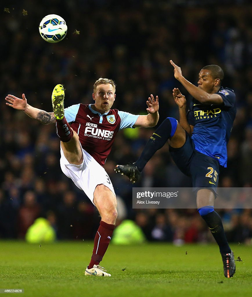 Scott Arfield of Burnley and Fernandinho of Manchester City battle for the ball during the Barclays Premier League match between Burnley and Manchester City at Turf Moor on March 14, 2015 in Burnley, England.