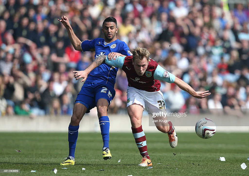 Scott Arfield of Burnley battles with Riyad Mahrez of Leicester City during the Sky Bet Championship match between Burnley and Leicester City at Turf Moor on March 29, 2014 in Burnley, England.