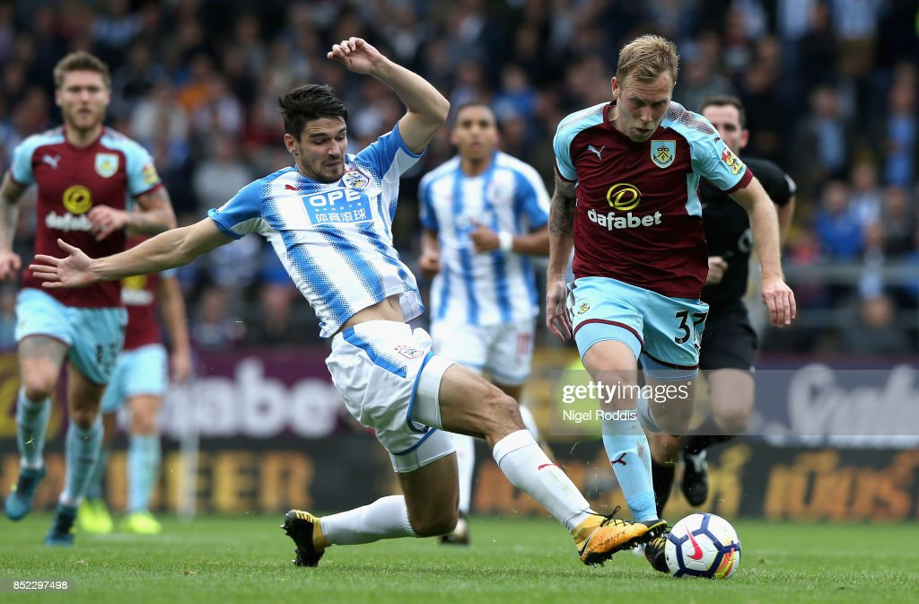 Scott Arfield of Burnley is tackled by Christopher Schindler of Huddersfield Town during the Premier League match between Burnley and Huddersfield Town at Turf Moor on September 23, 2017 in Burnley, England.