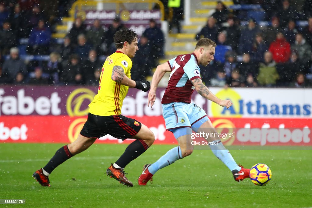 Scott Arfield of Burnley scores his sides first goal while under pressure from Daryl Janmaat of Watford during the Premier League match between Burnley and Watford at Turf Moor on December 9, 2017 in Burnley, England.